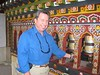 Spinning the prayer wheels which fill in the walls around an ancient temple in the border town of Phentsholing, Bhutan