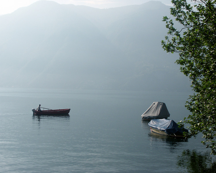 A fisherman in the early morning mist on Lake Lugano.
