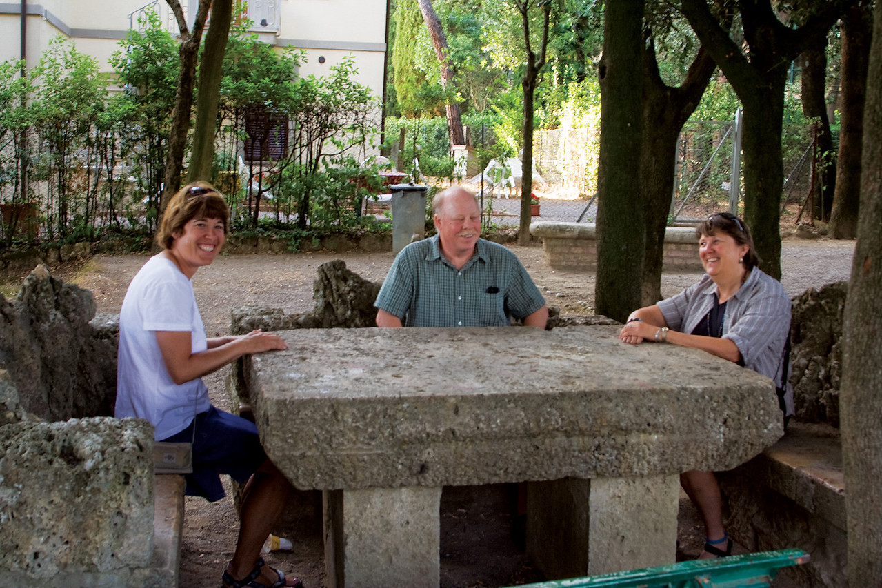 Jo, Steve and Tori relaxing at the stone table in a park in Chiusi