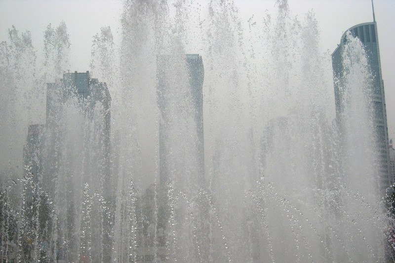 This is a view of the Shanghai skyscrapers as seen through a fountain outside the Shanghai museum.