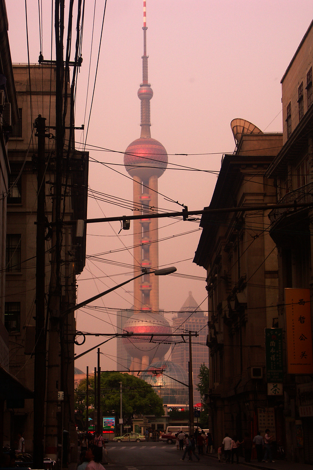 This view of the Oriental Pearl TV Tower gives a better view of the smoggy conditions that typically exist in Shanghai. It also demonstrates the contrasts (modern architecture in the midst of above-street electric poles) that exits there.