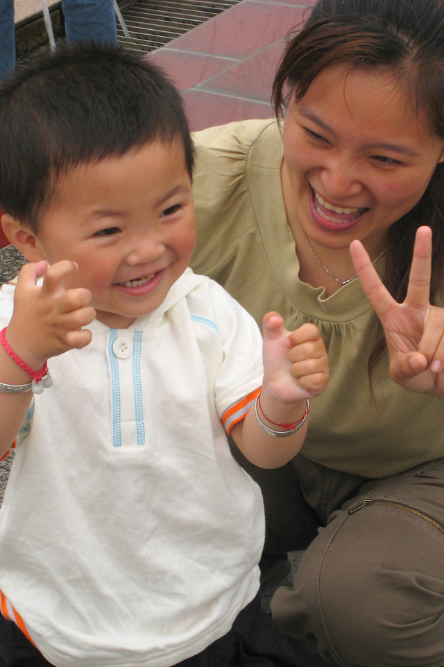 This last photo shows a mother and child posing for a family photo. I'm not sure why, but most Chinese, posing for photos, raise their fingers in the sign of a Vee. I'll let you ponder the reason.