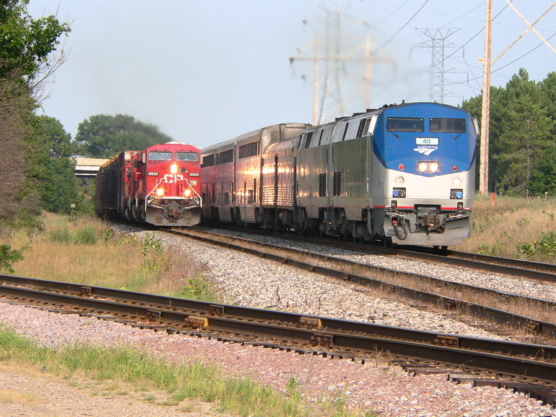 "Westbound Amtrak ""Empire Builder"" (Chgo to Seattle) barrels past a Canadian Pacific mixed freight just West of Portage WI."