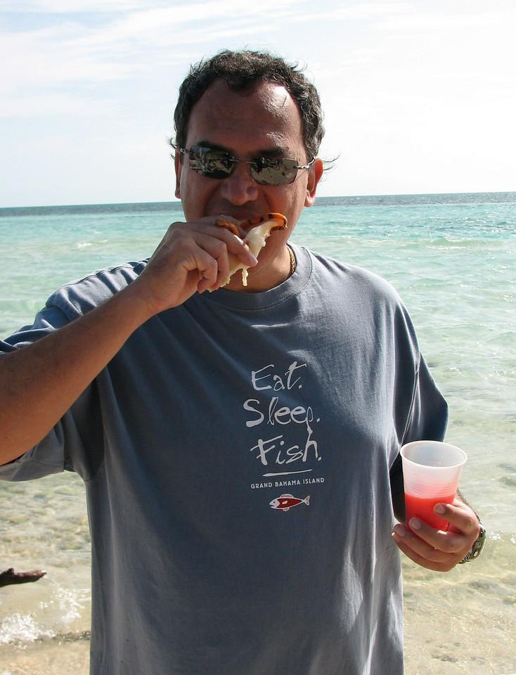 Cesar tries some very fresh conch, just cleaned by the tour guides.  There is no 'dinner impossible' for him.  <br /> <br /> Cesar prueba un caracol fresquisimo, luego de ser limpiado por uno de los guias del tour.  Para el no existe la 'cena imposible'.