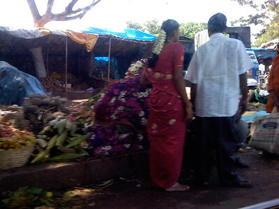 Thursday. Many beautiful flower garlands on sale beside the road. Behind are crude stalls with more fruits and vegetables. India. Bangalore.