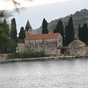"In the middle of Kotor Bay sits ""Our Lady of the Rocks"" shrine.  It was built on a man made island and contains a treasure of 17th century artwork."