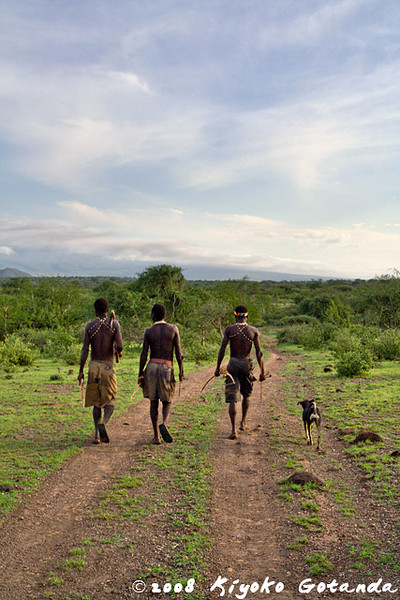 Hadzabe with their dog look for potential animals to hunt
