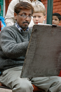 Andy watches a street artist in Delhi. He later had his own sketch made. [Delhi]