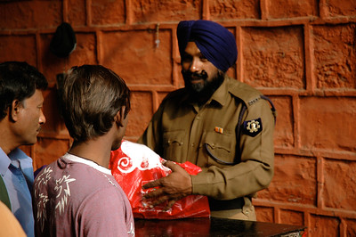Sikh guard inspecting packages, inside Red Fort. [Delhi]