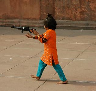 a child plays with a toy machine gun (?), Jama Masjid mosque. [Delhi]