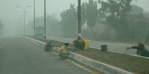 despite the fog, these workers paint the median strip with no protection. Dharamsala to Delhi. Himachal Pradesh.