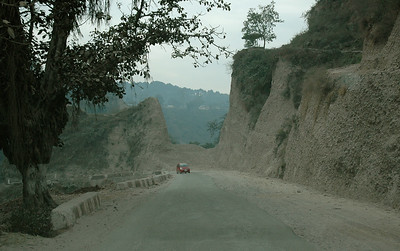 On the return, the landscape was carved by glacial rivers. Here they are slowly digging out the hillside to straighten and widen the road. Dharamsala to Delhi. Himachal Pradesh.