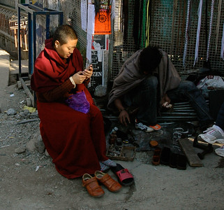Dharamsala: a monk checks her cellphone while waiting on a shoeshine.
