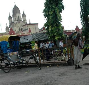 Outside Dakshineswar Kali Temple: an old man, with his bag and his umbrella. temple at rear. Kolkata.