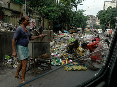 "Trash is routinely dumped along the road – and ""rag pickers"" seek items they can use or sell; Kolkata."