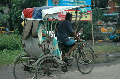 Rickshaw with extended cover; it rains a lot in Kolkata.