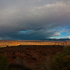 The sun goes down over the horizon with the La Sal Mountains as the eastern backdrop to the park.
