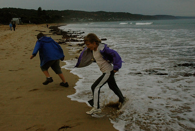 John and Mara dash when a wave catches them by surprise, along the Great Ocean Road; Victoria, Australia.