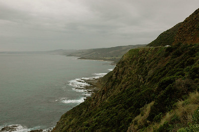 The road often hugs to the steep hillsides, as it does here. Australia Great Ocean Road.