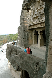 Andy and Pam at Ellora caves, examining one carved entryway; upper-left corner has a huge beehive.