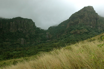 beyond the grassland, cliffs and a waterfall; summits are in clouds. (Abaca village, near Lautoka, Fiji.)