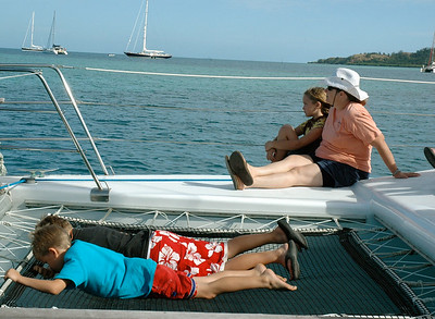 John and Andy watching through the catamaran's net, while Mara and Pam enjoy the scenery at Malolo lailai island, Fiji.