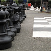 Plastic chessmen lined up next to 8'x8' board. The area also has gigantic checkers pieces.