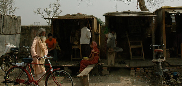 On our way to Agra: a pilgrim passes roadside huts.