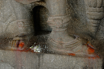 Shravanabelagola: at the feet of the temple guardians, visitors place rice at his feet, and colored powder on his big toe.
