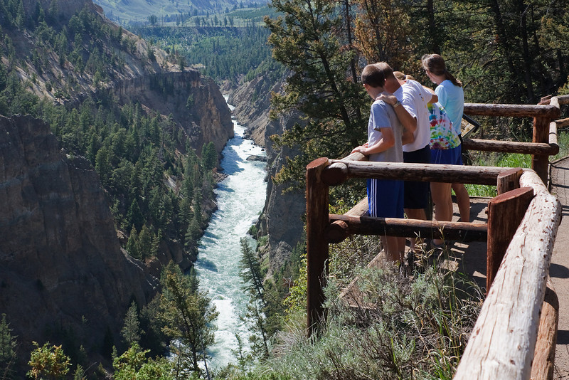 Family looking at the Yellowstone River flowing through Yellowstone Canyon