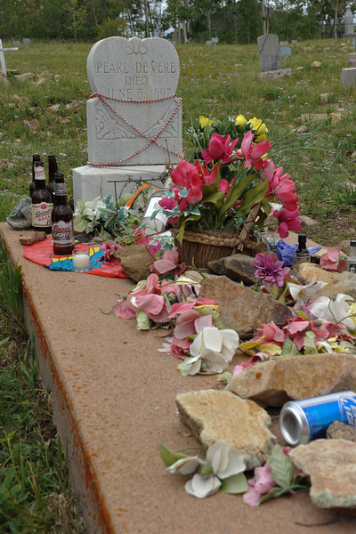 Grave site of Pearl DeVere adorned with various items.  Google her name and learn of her colorful occupation and life which will explain the unusual items for a grave site.