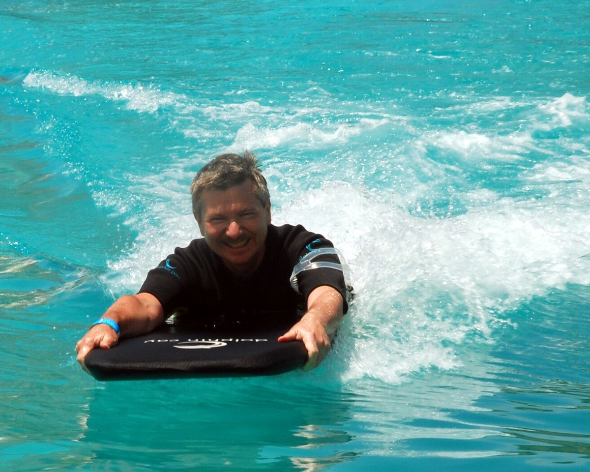 Dolphin pushing Ladd on boogie board.
