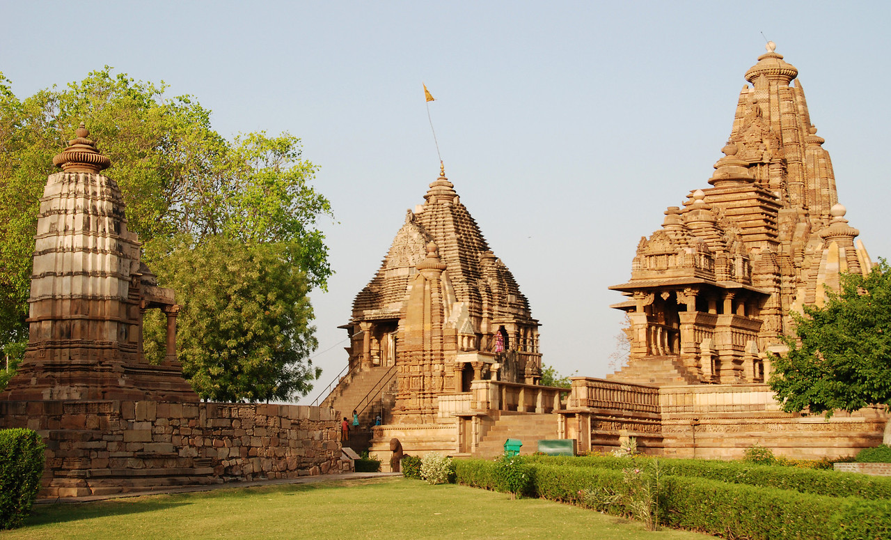 A small portion of the Chandelas Hindu temple complex in Khajuraho.  The building in the center is an active temple. The building on the right contains thousands of sculptured panels on its external walls, some of which are quite erotic.