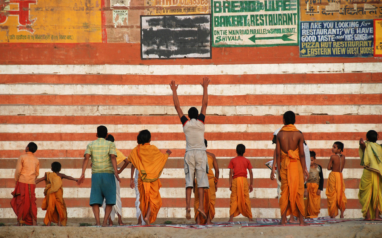 Group yoga exercises on the bank of the Ganges.