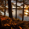 The last sliver of sun casts an orange glow across the lake and campsite.