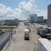 """Utsikt fra gangbrua ved ISS-bygningen mot andre deler av romsenteret. Bygningen bak til høyre er bygningen der astronautene blir tatt imot etter endt tur. Gjerdet til venstre skulle visstnok beskytte mot """"gators"""" (alligatorer), men hvem vet..."""