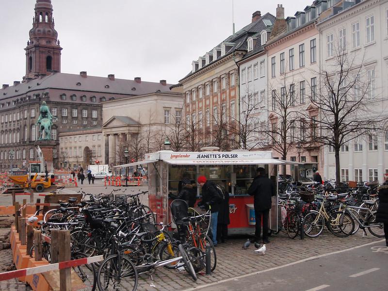 Det var mange slike pølseboder i byen, der folk hang og spiste pølser og hotdogs, gjerne med en klatt ketchup og sennep på papir, eller diverse annet tilbehør. Her ved Højbro Plads. Christiansborg i bakgrunnen.