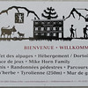 Switz001 In this simulated cut-paper sign, they have a quick summary of Switzerland   Mountains, cows, goats, trams and more mountains, all in multiple languages (English, German, French and Italian)