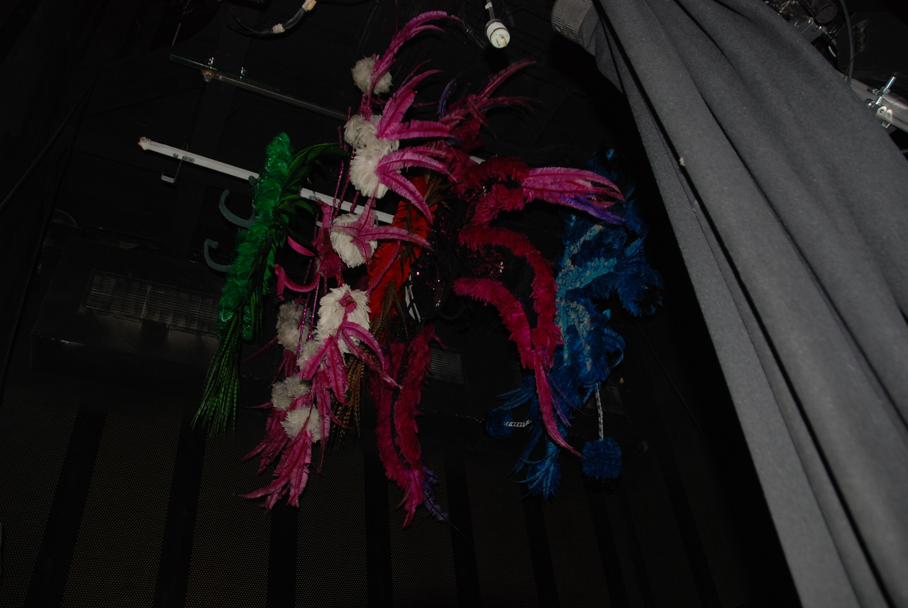 Head dresses hang from the ceiling for storage.