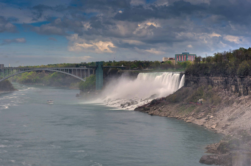 The American Falls with the Rainbow Bridge at Niagara Falls is an international steel arch bridge across the Niagara River gorge, and is a world-famous tourist site. It connects the cities of Niagara Falls, New York, United States (to the east), and Niagara Falls, Ontario, Canada (west).
