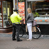 She is getting a ticket for riding her bike in a pedestrian area.