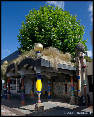 """Exterior of the Hundertwasser public toilets in Kawakawa.<br /> <br /> The appearance of a """"green roof"""" of the public toilet shows Hundertwasser's use of nature as well as natural shapes in his work.  (It is actually a tree with planted in the middle of the entrance area to the toilets.)<br /> <br /> Kawakawa,  NZ<br /> November 19, 2011<br /> 066"""