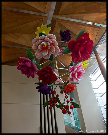 Flower chandalier by Choi Jeong Hwa.  The flowers in this chandalier in the Auckland Art Museaum rise and fall as they are inflated and deflated in sequence.  <br /> <br /> Kauri trees (already dead) provided the wood for the ceiling of the lobby.<br /> <br /> Auckland, NZ<br /> December 4, 2011