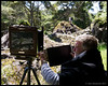 A photographer using actual film and an 8x10 view camera making engagement photos of a couple at on the Wairere Boulders.<br /> <br /> Wairere Boulders Nature Park<br /> Hokianga, NZ<br /> November 19, 2011