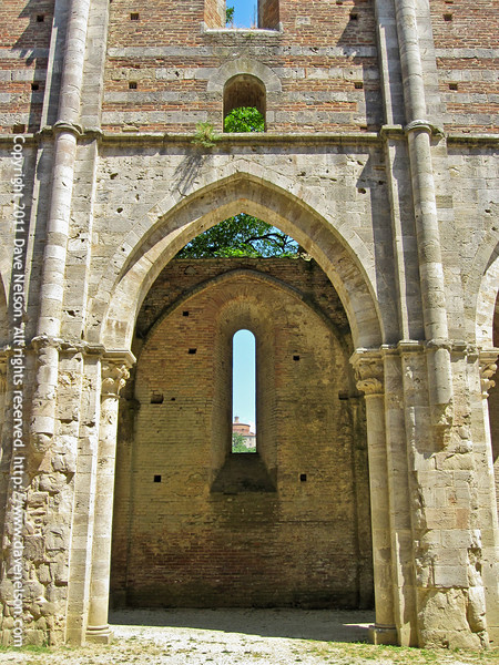 Looking through a window of the Abbey to Montesiepi
