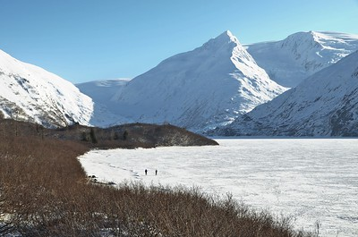 Two people walk across the ice of Portage Lake, Alaska March 2011