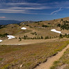 The view of the Obstruction Point trailhead that is a high saddle that leads to many interesting day and overnight trips. This trailhead is 8 miles from the Hurricane Ridge visitor center along a winding single lane gravel road seen winding into the distance.