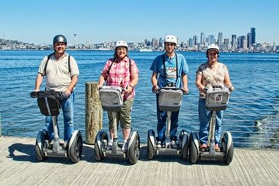 Dale and Colleen Easley, Zach and Jennifer Vaughn riding their Segways in West Seattle with Seattle skyline in the background.
