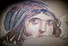"Zeugma Mozaik Muzesi, Gaziantep<br /> <br /> The Gypsy Girl Mosaic, 2nd-3rd Century A.D., The House of Menad. <br /> This is arguably the museum's most prized mosaic. It has been been called ""The Mona Lisa of the East"", because of the bewitching way her eyes move as you move as does the Mona Lisa.<br /> <br /> The mosaic museum is gorgeous. The curators have for the most part done a fantastic job displaying their collections. Having said that, I am disappointed with how the Gypsy Girl is displayed though. First, she is hanging in a receded wall at the far end of a completely darken room; She is the only object n the room. As soon as you walk into the room, a bell rings and in walk a museum security guard. He stays in the room with you until you're done. Of course there's nothing wrong with that. My major gripe is how the Gypsy Girl is lit. When I first saw her in the room I thought it was either a fuzzy projected image of her on the wall, or it was a flat TV screen with a fuzzy image of her. Only after talking with other tourists in the room was I then made aware that I was looking at the real deal. The lighting used completely washes her out; It was as if she was lit by florescent lamp. So for all of the hype I had heard about the Gypsy Girl, I was left somewhat disappointed after seeing the real thing up close."