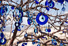 Evil eye ornaments hanging on an outdoor tree, Uchisar